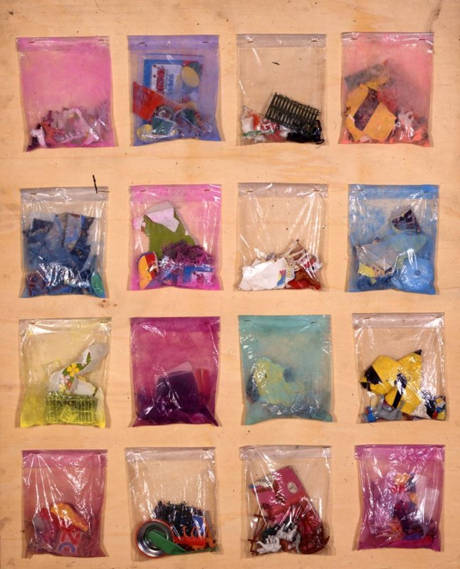SACCHETTINI – Senza titolo, 1956 Sacchettini di plastica con all'interno vari oggetti, fissati su tavola cm 102, 3 x 82,3 Collezione privata