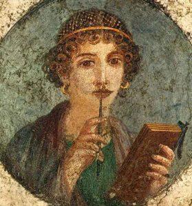Tondo-con-Donna-con-tavolette-cerate-e-stilo,-Particolare,-55-d.C.,-Museo-Archeologico-Nazionale-di-Napoli---Public-Domain-via-Wikipedia-Commons